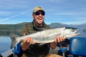 Man smiles while holding chum salmon, Johnstone Strait, BC
