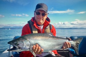 Smiling man in hat with chinook salmon