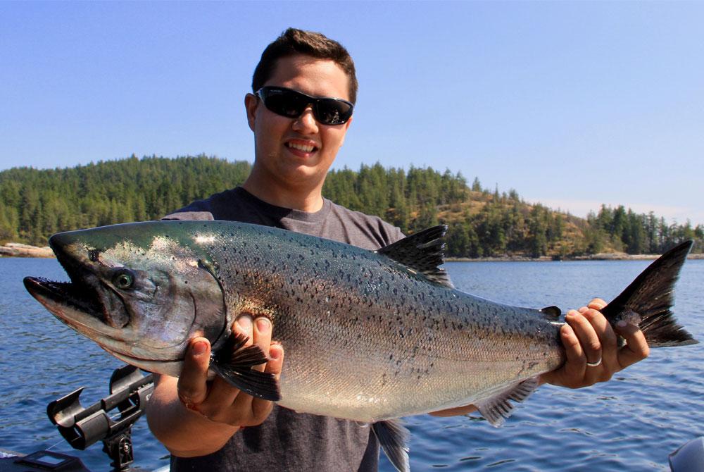 Man in sunglasses holds chinook salmon