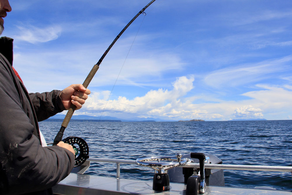 Man holds salmon rod and fights fish with islands in background