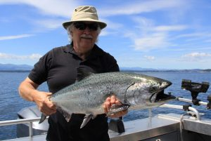 Man in hat holds chinook salmon on boat near Campbell River, BC