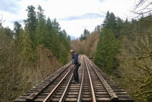 Angler with fly rod stands on railroad trestle and looks over