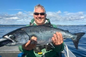 Man smiles and holds chinook salmon near Campbell River, BC