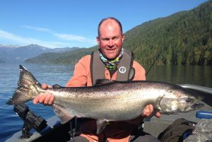 Man holds large chinook salmon in Johnstone Strait, BC