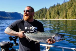 Man in black t-shirt holds chinook salmon and smiles
