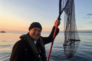 Man in toque holds fishing net with boat in background