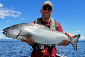 Man in baseball hat holds large chinook Salmon near Campbell River, BC