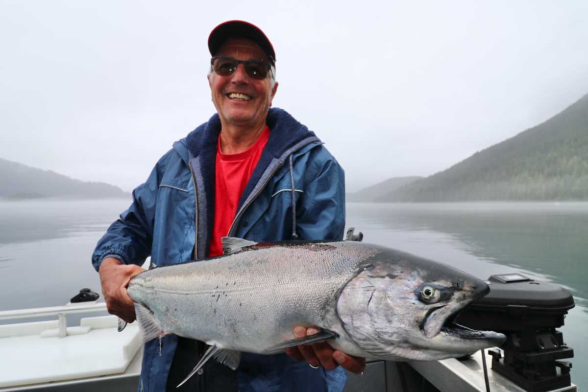 Man Holding Chinook Salmon in Mist